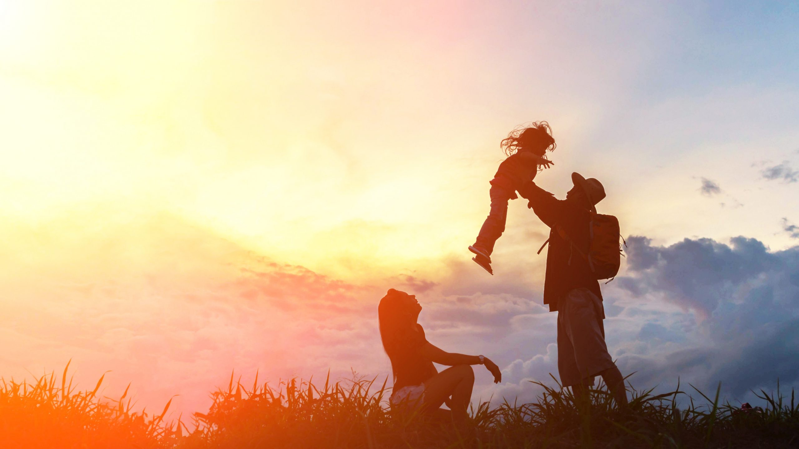 The happy family of three people, mother, father and child in front of a sunset sky.